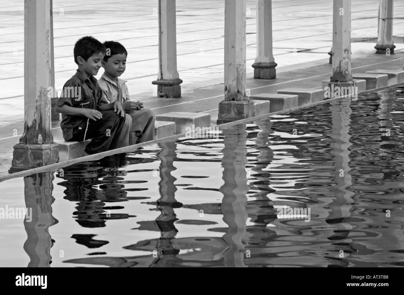 Two Boys Gossiping and Washing at the Jami Masjid Mosque in Ahmedabad, Gujarat India - Stock Image