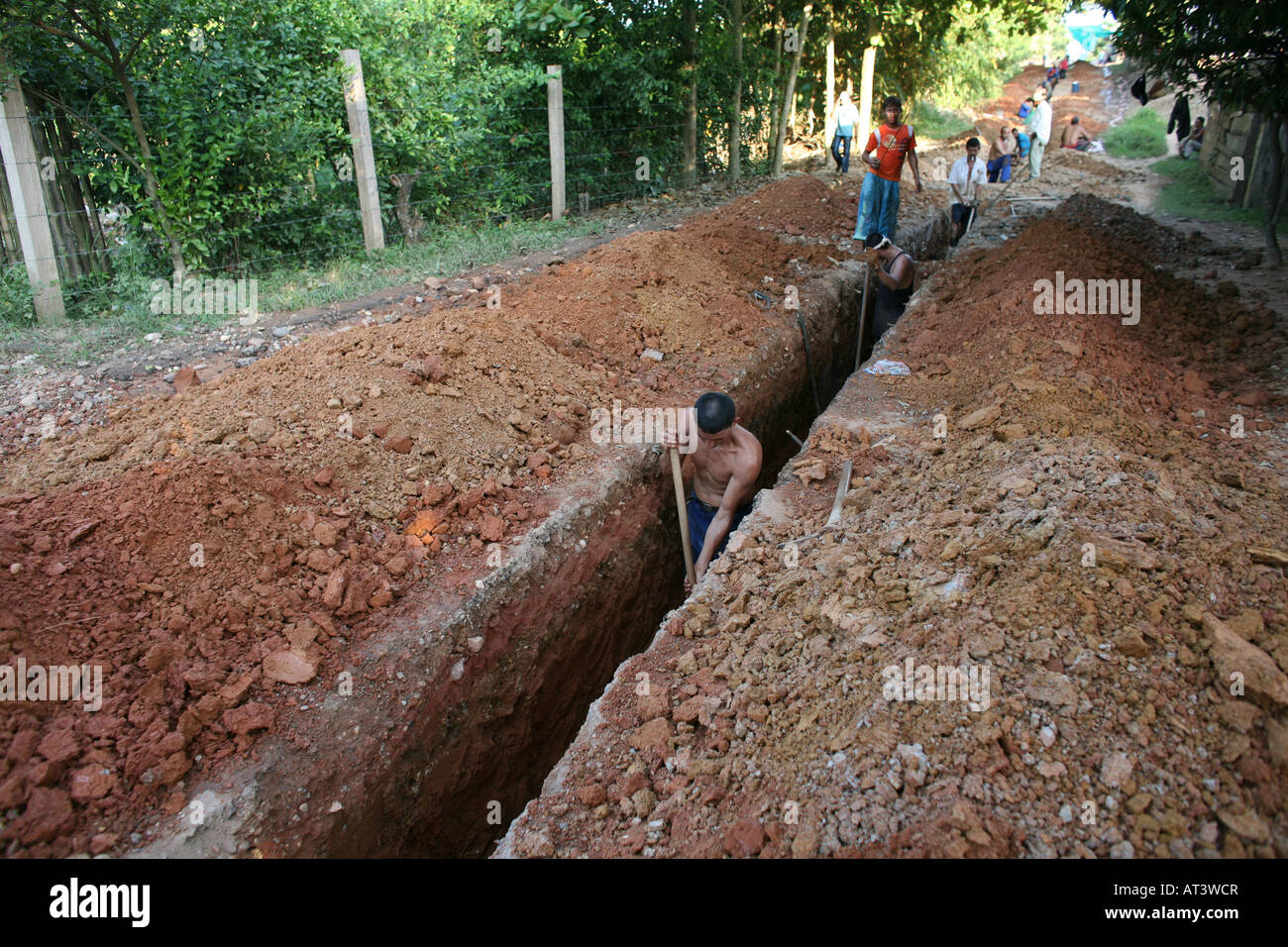 Poor communities building a sewerage system in their slum The government provides the materials - Stock Image