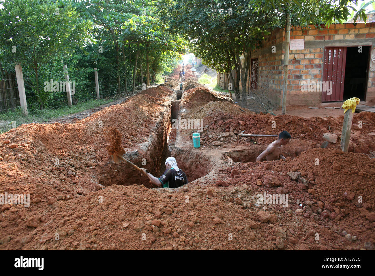Poor communities building a sewerage system in their slum The government provides the materials Stock Photo