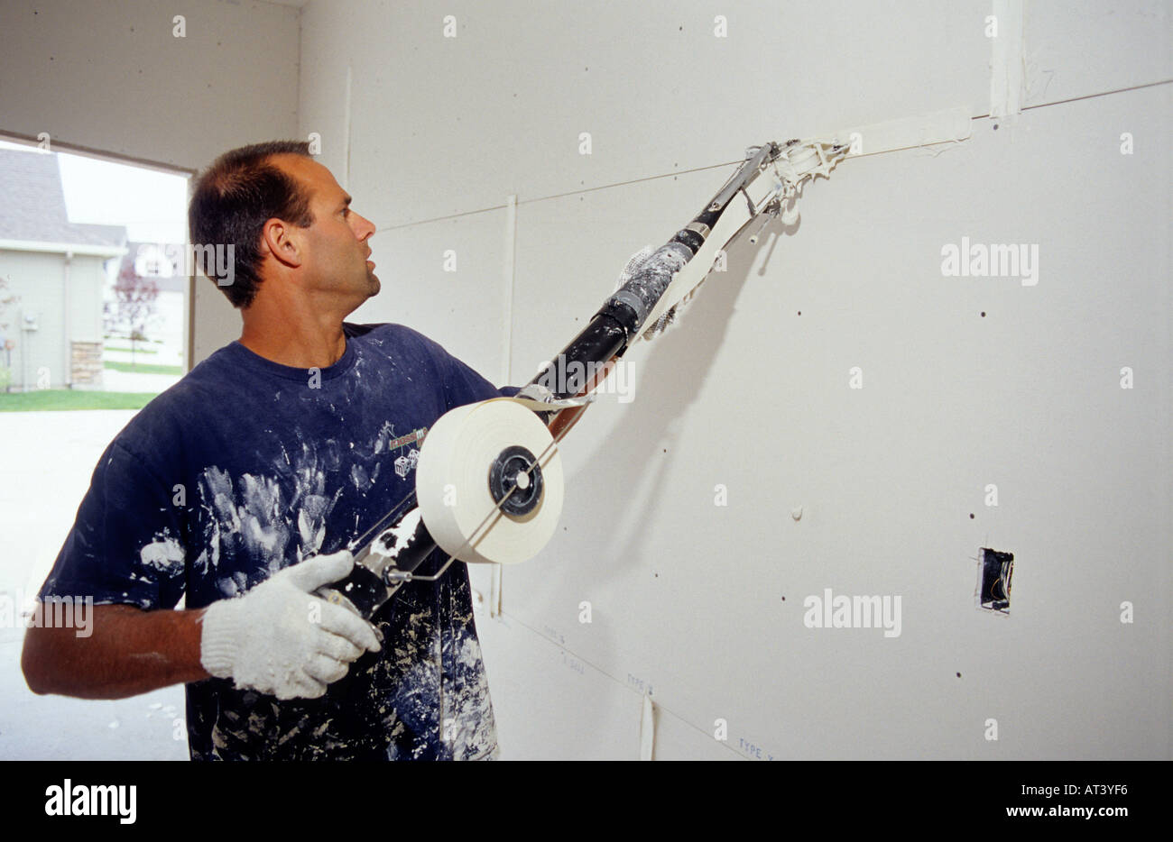 A Dry Wall Worker Uses A Drywall Tape Applicator Called A