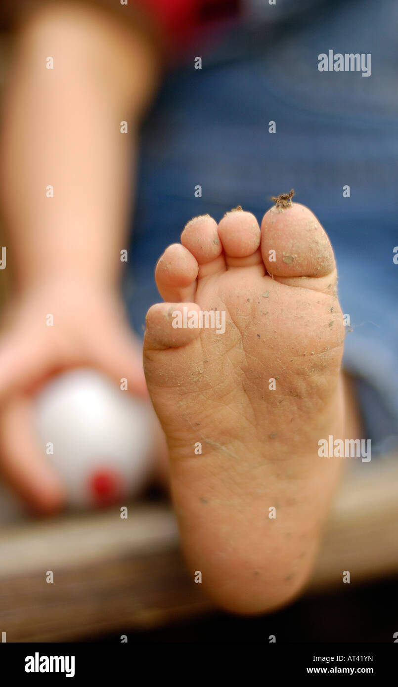 Toddlers dirty foot and fishing bobber - Stock Image