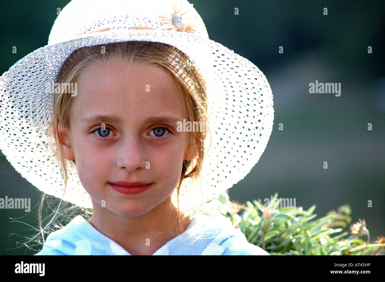 Royalty free photograph of British young girl on summer holiday in sunshine wearing a sun hat and posing for a portrait. - Stock Image