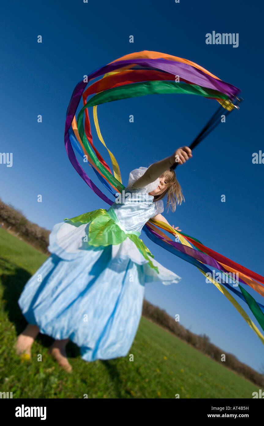 Child jumping and spinning with streamers - Stock Image