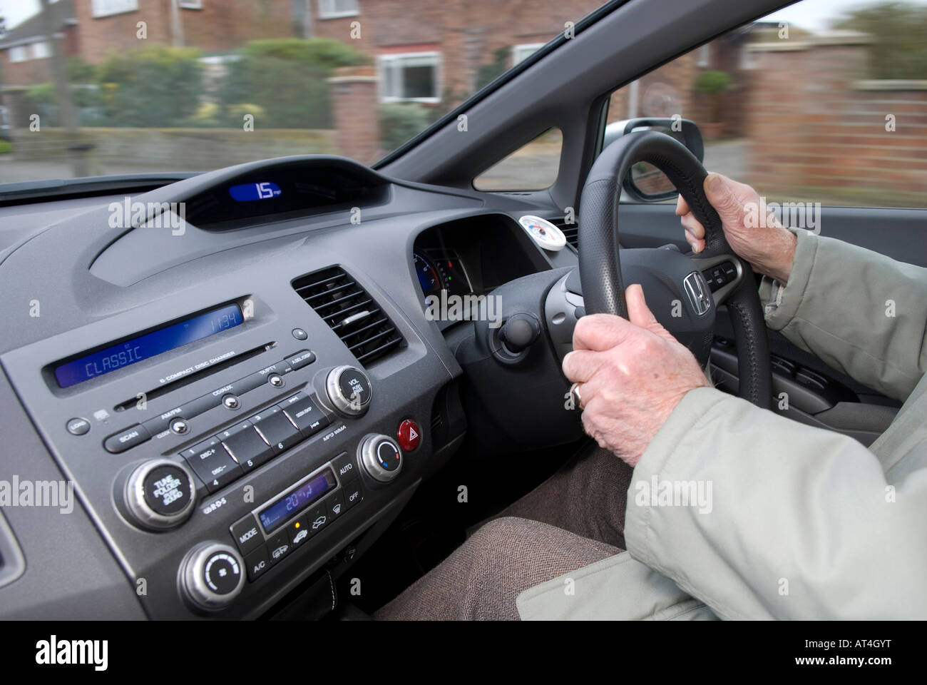 retired person driving hybrid motor car - Stock Image