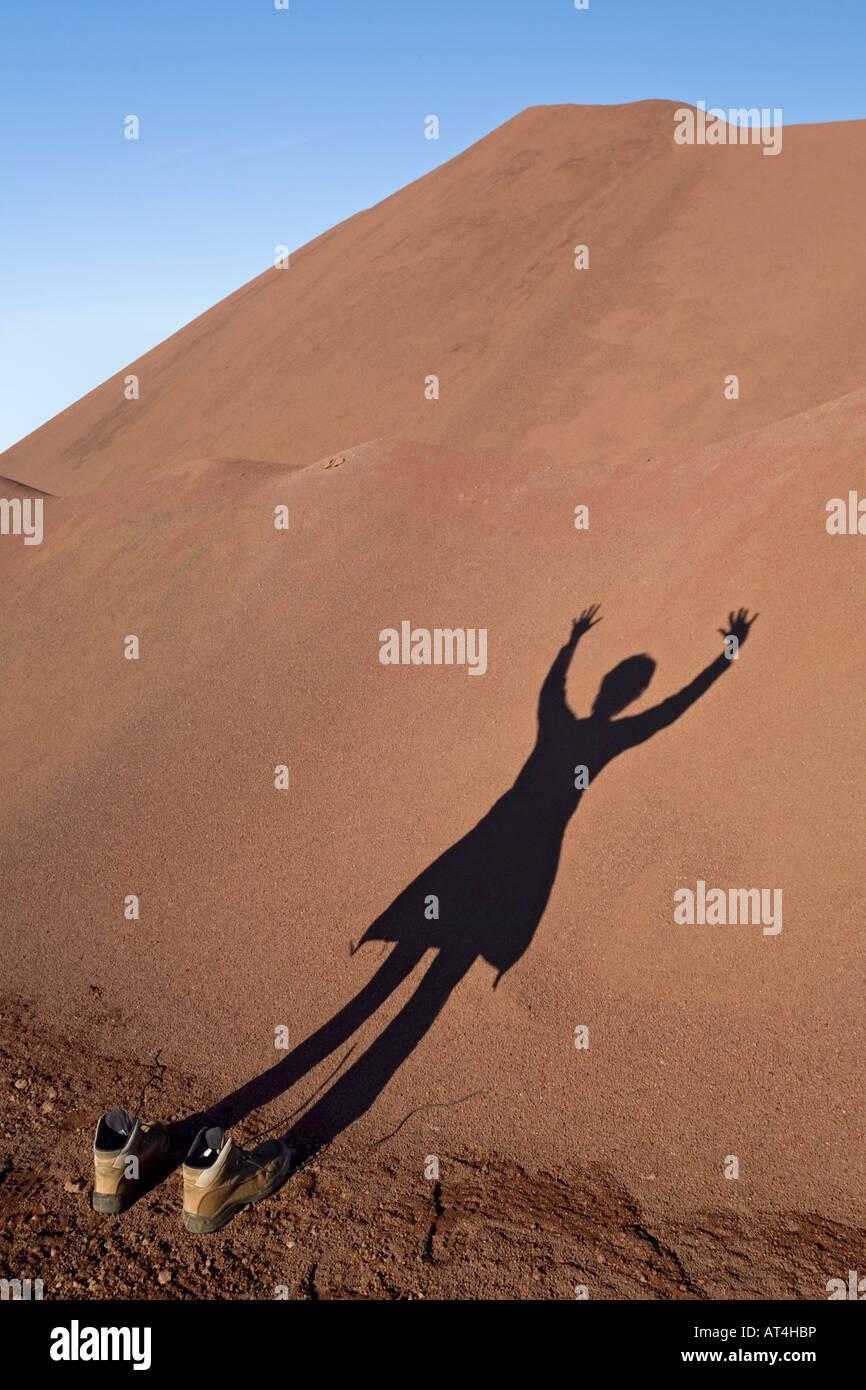 The shadow of a young Lady on a pozzolana heap. Ombre d'une jeune femme projetée sur un tas de pouzzolane. - Stock Image