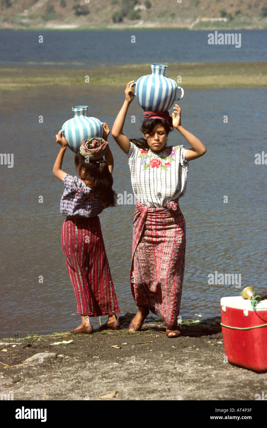 Guatemala Santiago Atitlan two women collecting drinking water from Lake Atitlan shore - Stock Image