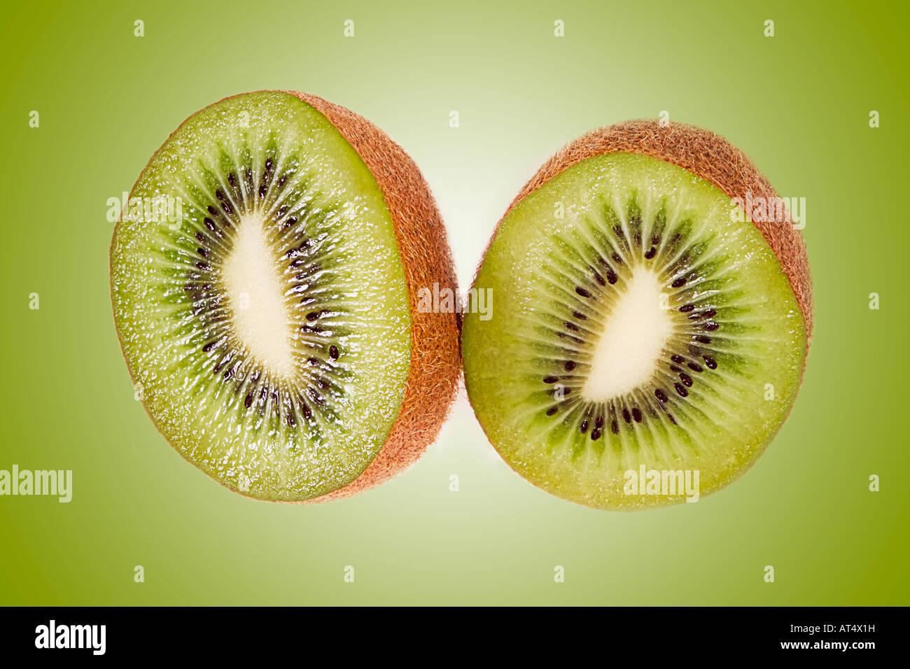 Two kiwi fruit cut on matching green background - Stock Image