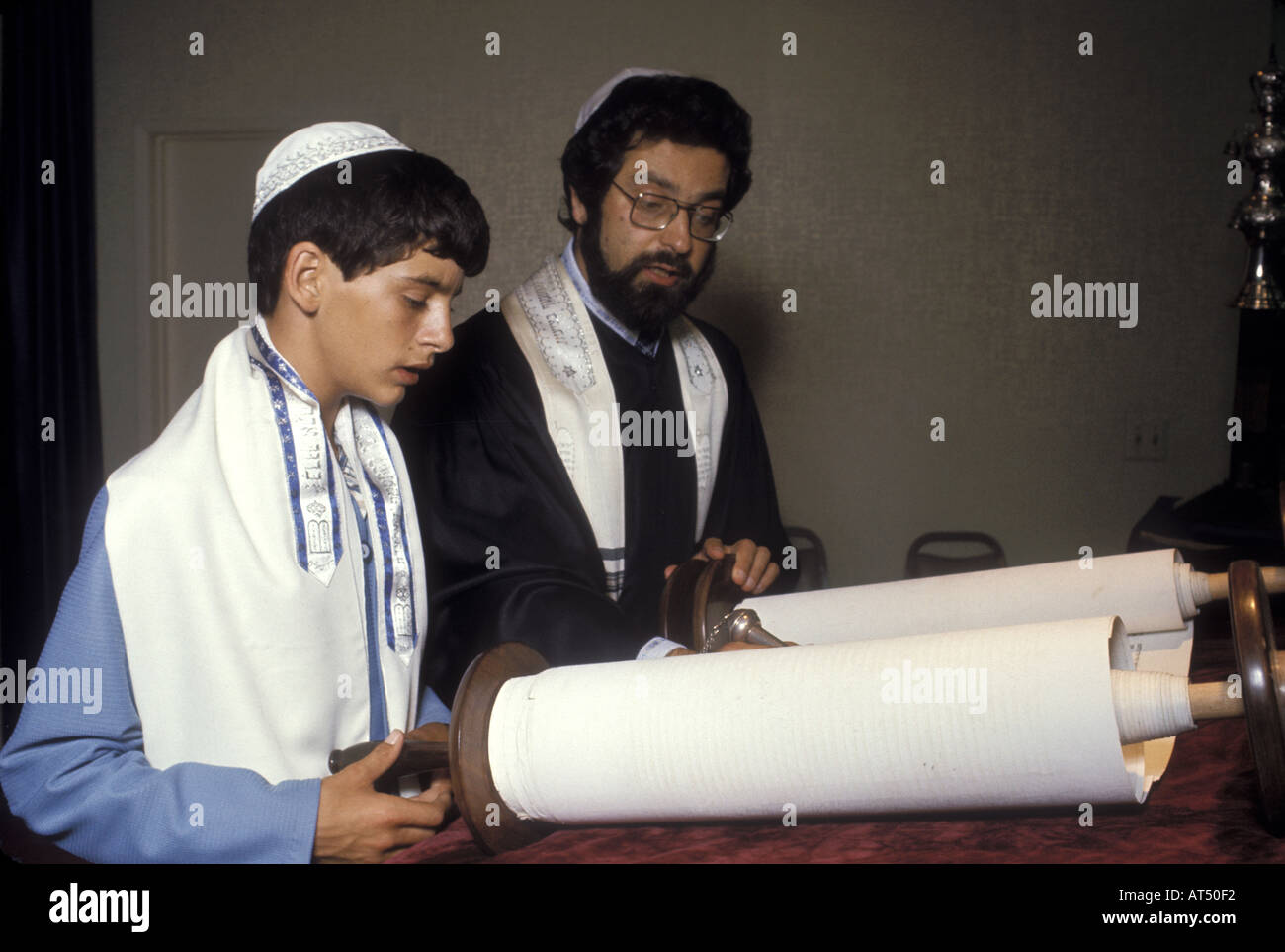 Rabbi and teenager reading from the Torah - Stock Image