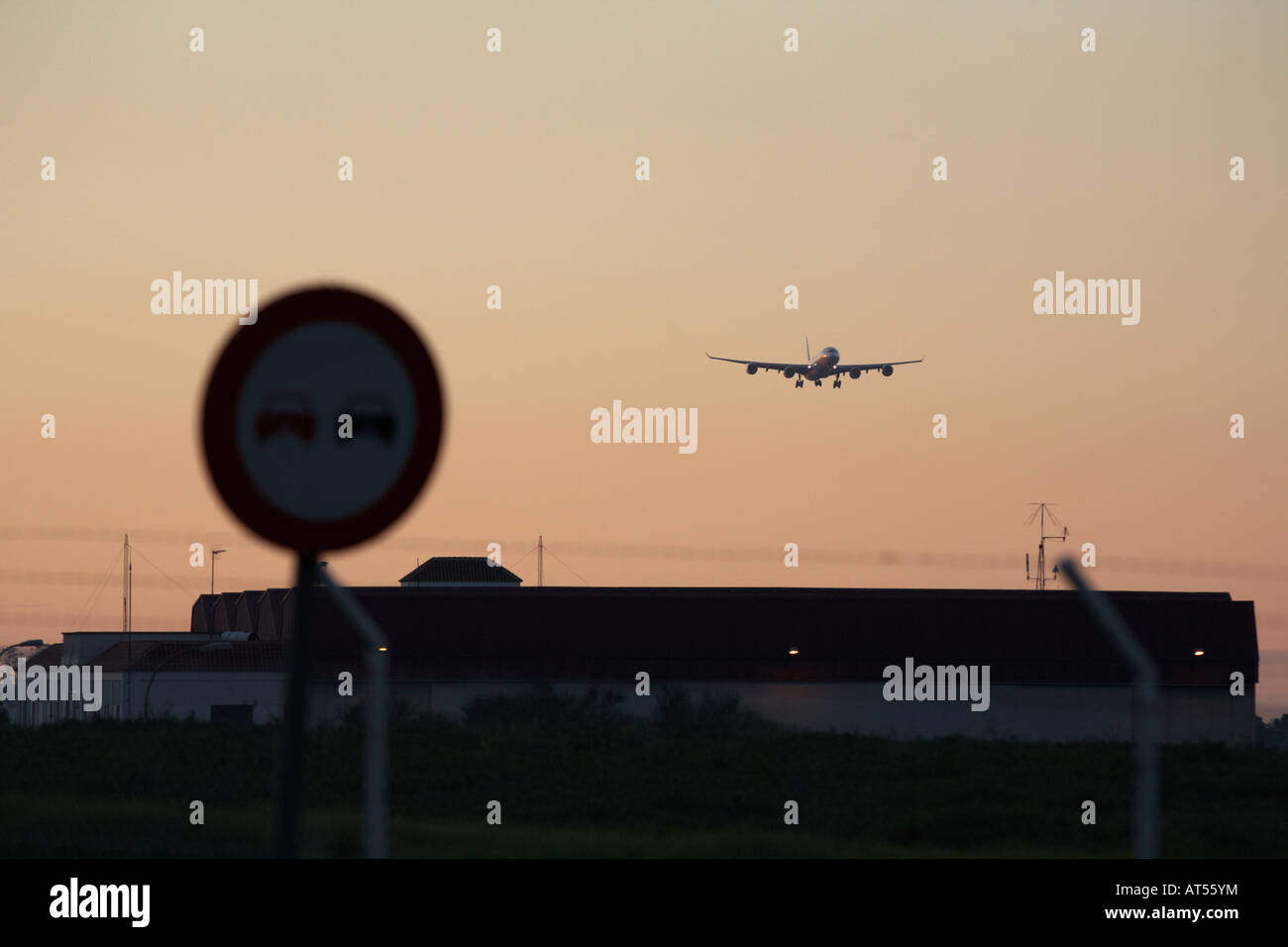 aircraft on final approach in evening light over perimeter fence buildings near Los Rodeos Tenerife North TFN airport - Stock Image