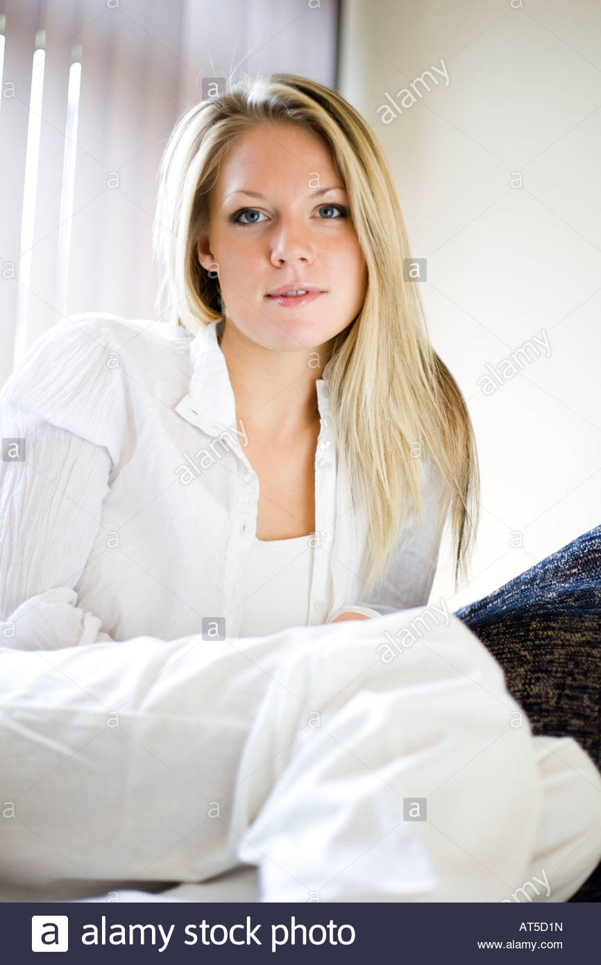 Young woman relaxing looking at camera in lifestyle environment - Stock Image