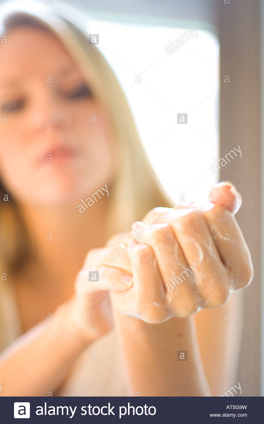 Young woman moiturises her hands with cream - Stock Image