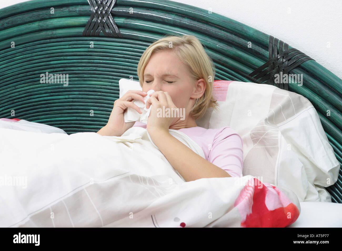 Kranke Frau putzt Nase Stock Photo