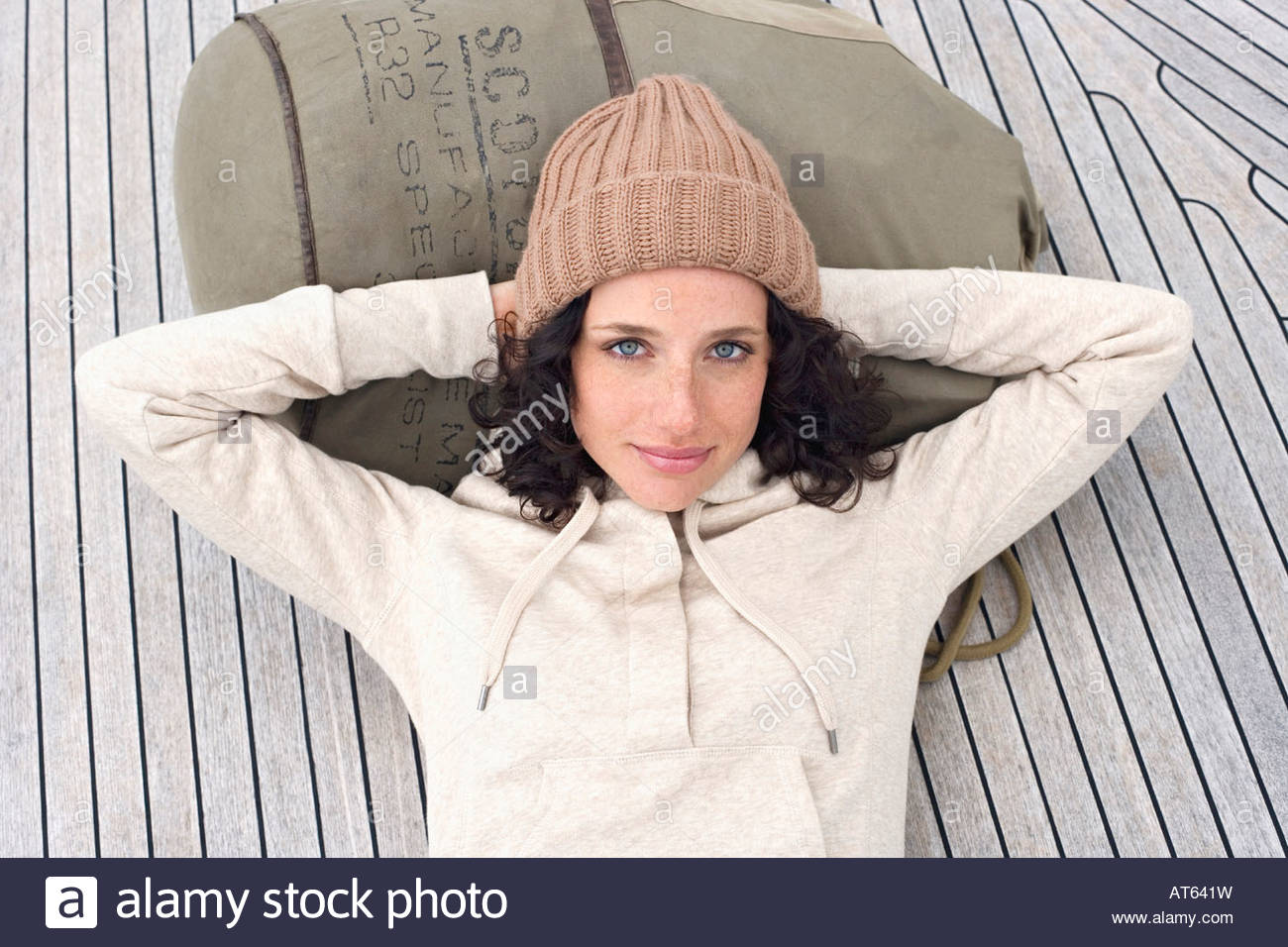 Germany, Baltic Sea, Lübecker Bucht, Portrait of a young woman lying on deck of yacht, smiling - Stock Image