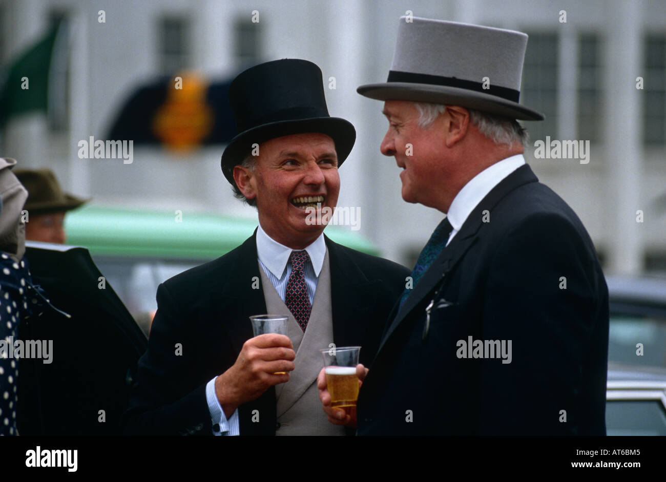 Two men drinking champagne at a picnic in the car park on Derby Day at Epsom racecourse, Surrey UK - Stock Image