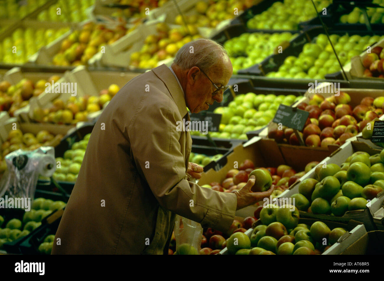 A man looking at apples in the fruit and vegetable section of an ASDA supermarket in Dewsbury,Yorkshire, England - Stock Image