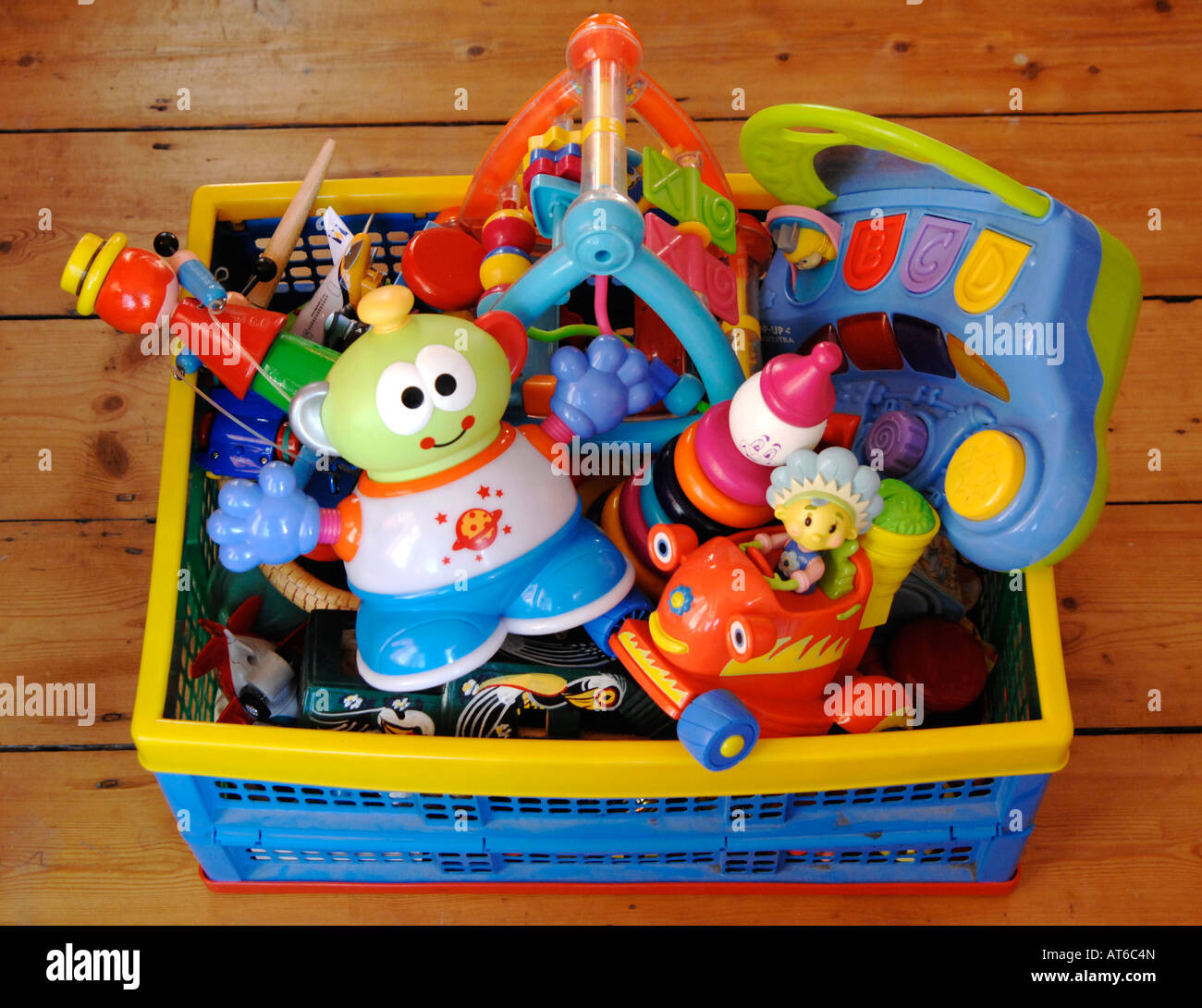 Crate of colourful plastic children's toys - Stock Image
