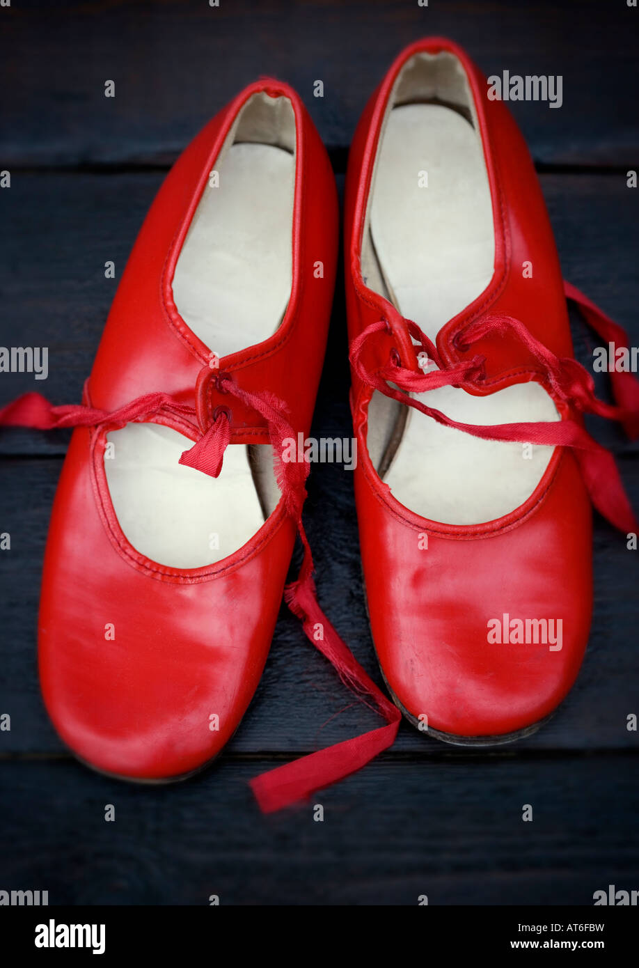 A pair of vintage red tap shoes shot against polished dark wooden floor boards - Stock Image