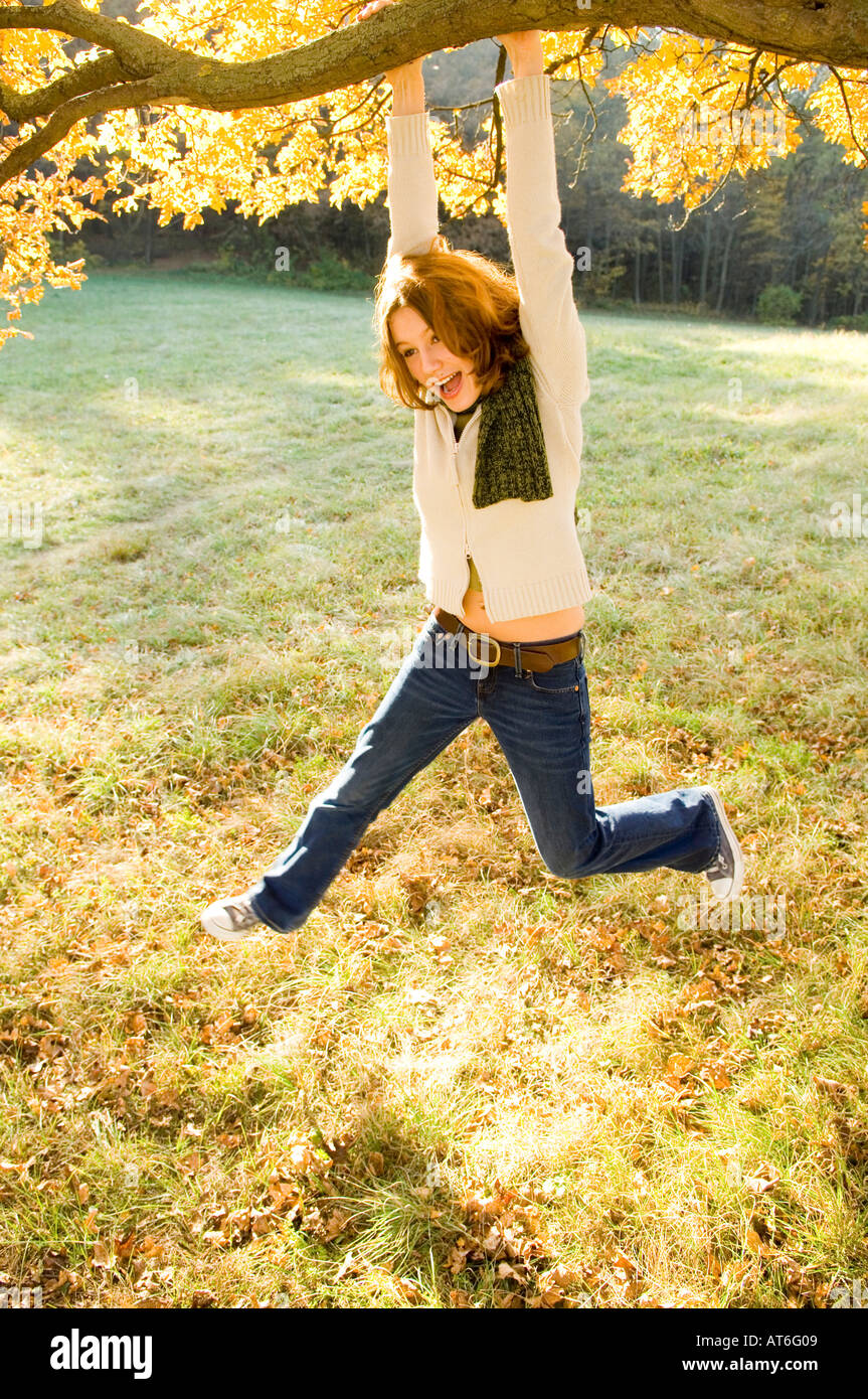 young woman/twen outdoors, hanging on a branch - Stock Image