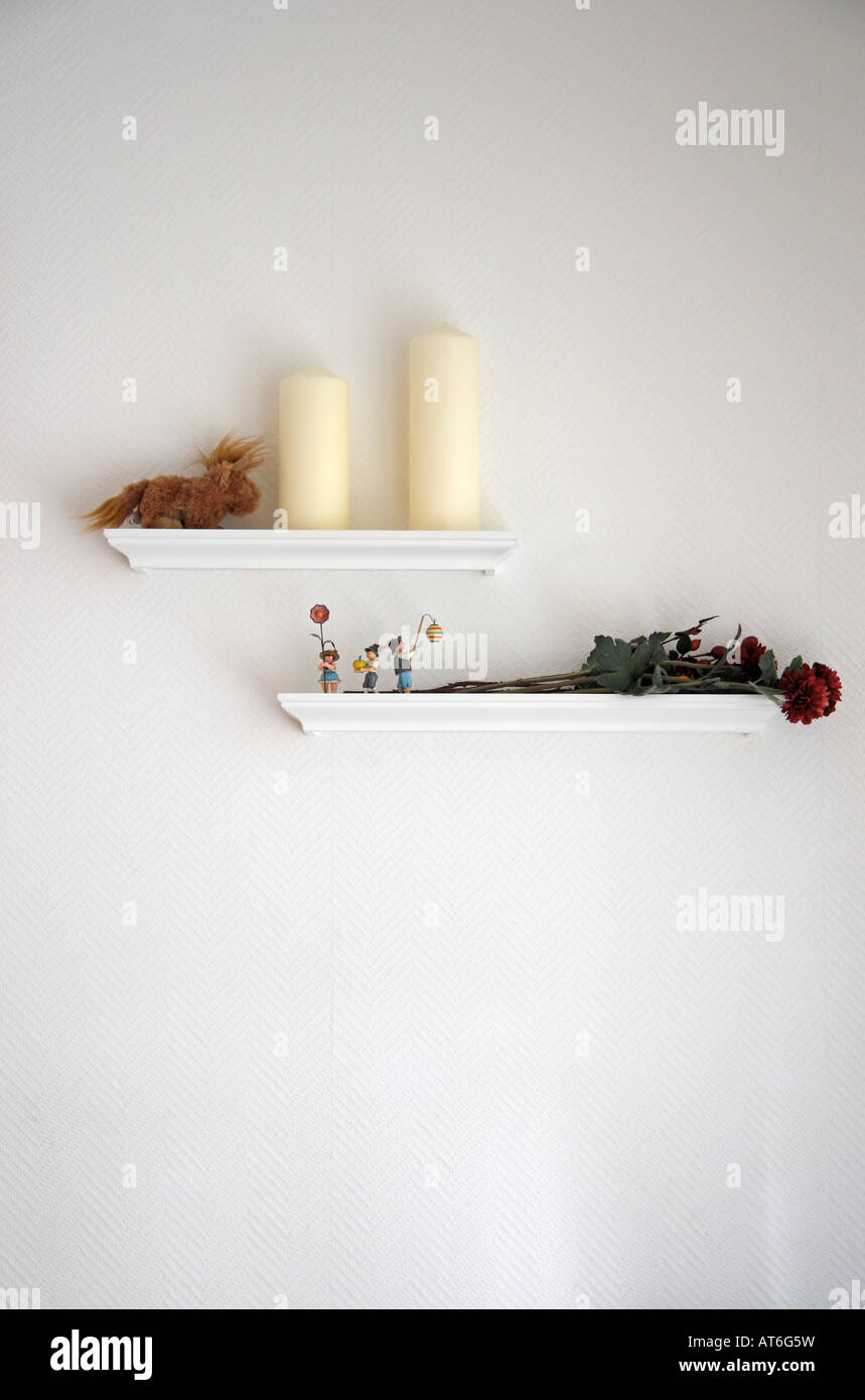 Dried rose and candles on shelf - Stock Image
