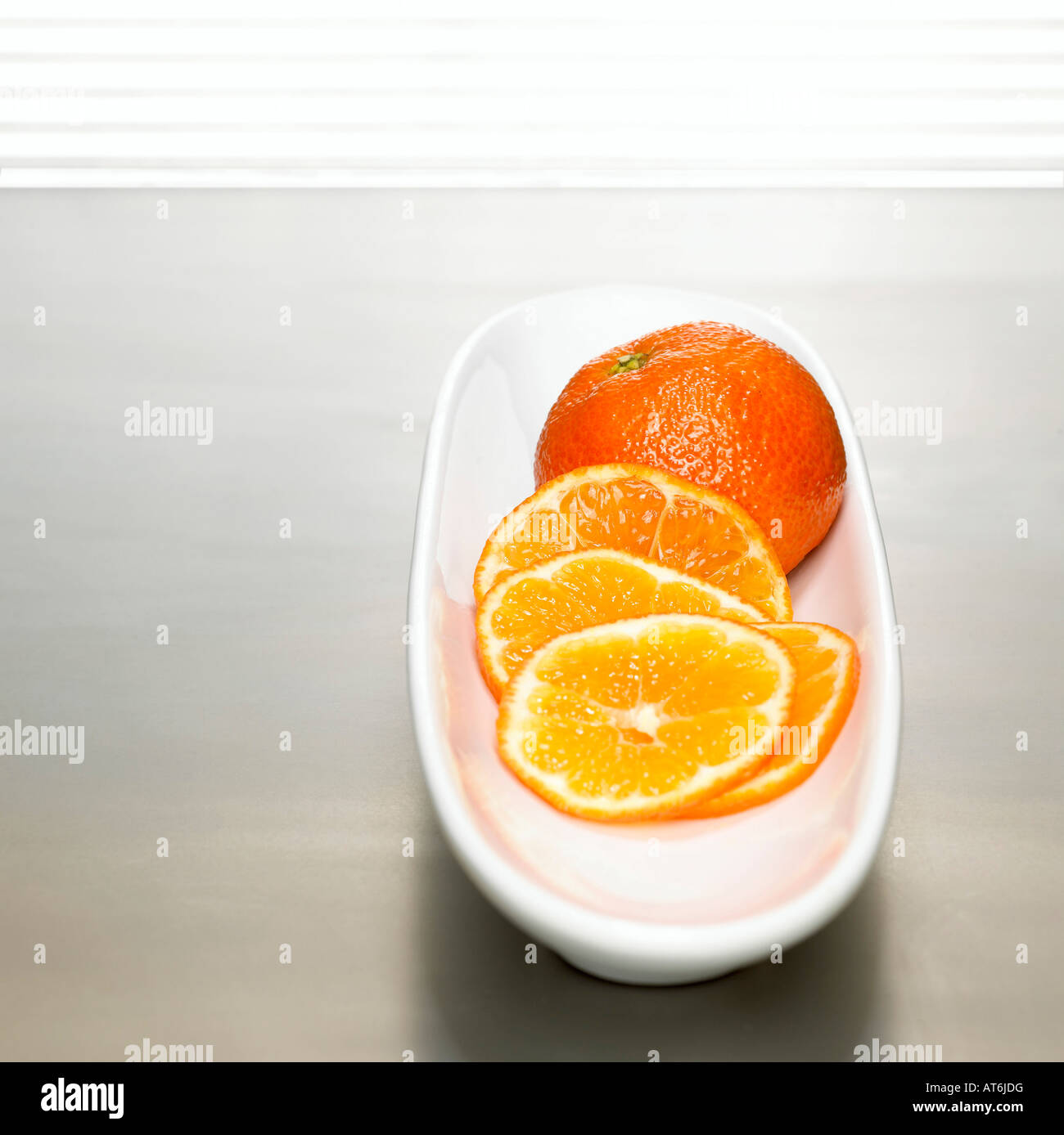Sliced tangerines on bowl, close-up - Stock Image