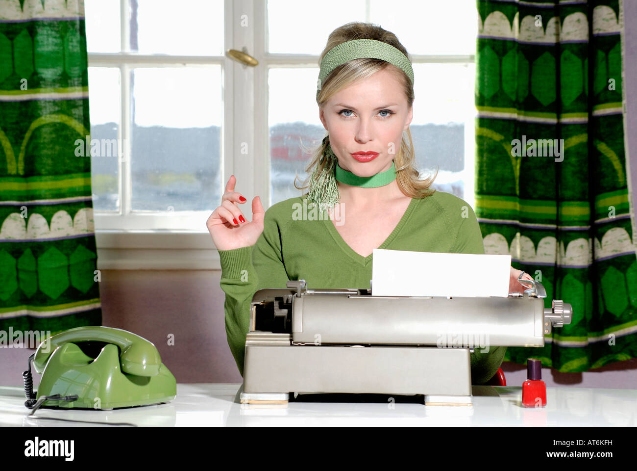 Young woman sitting at desk, close-up - Stock Image
