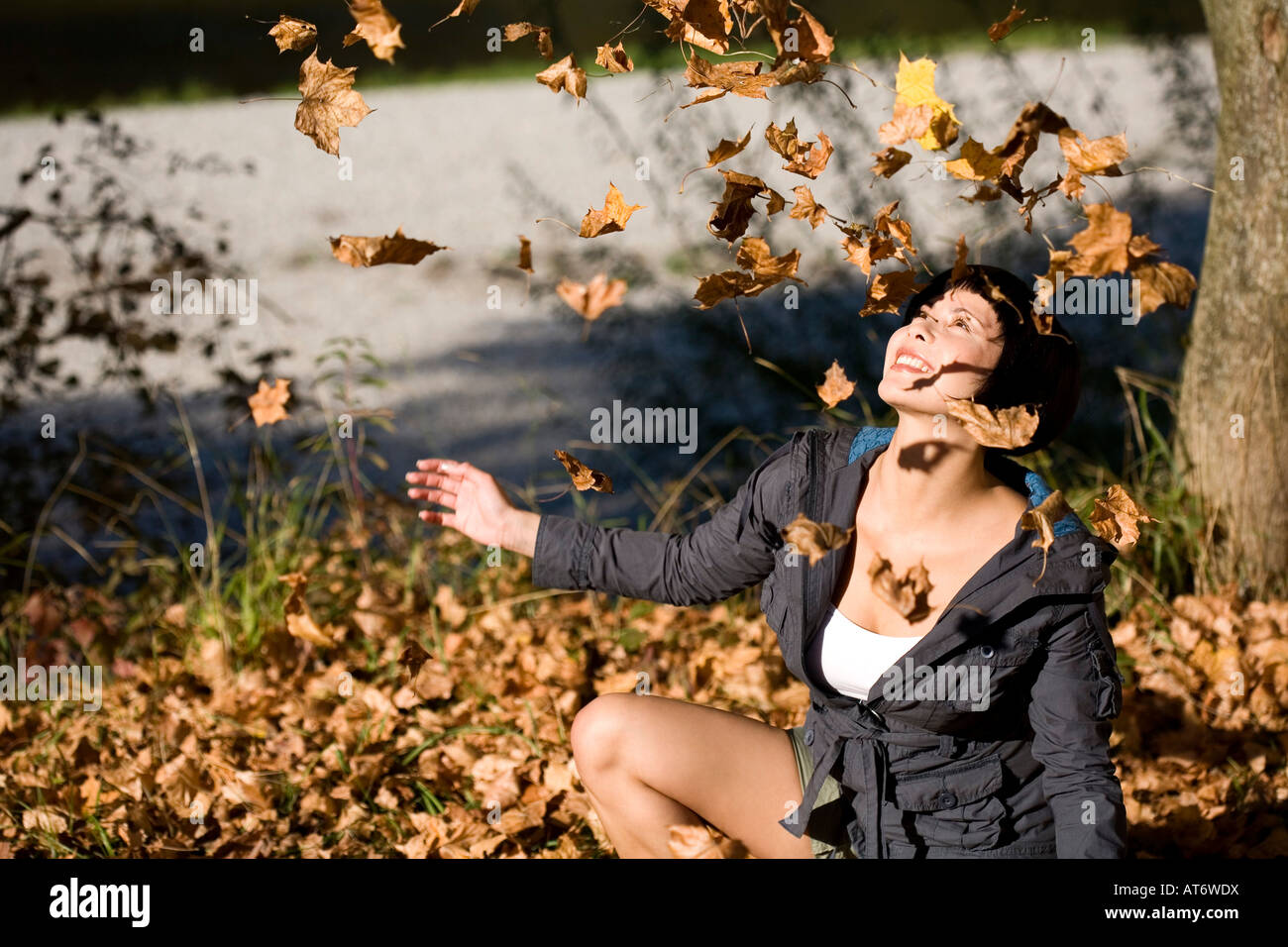 Germany, Bavaria, Young woman looking at falling Autumn leaves, portrait - Stock Image