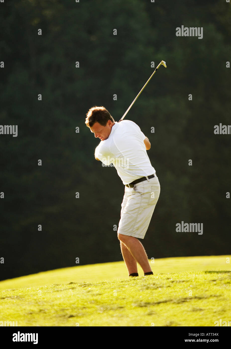 Austria, Male golfer swinging club on fairway - Stock Image