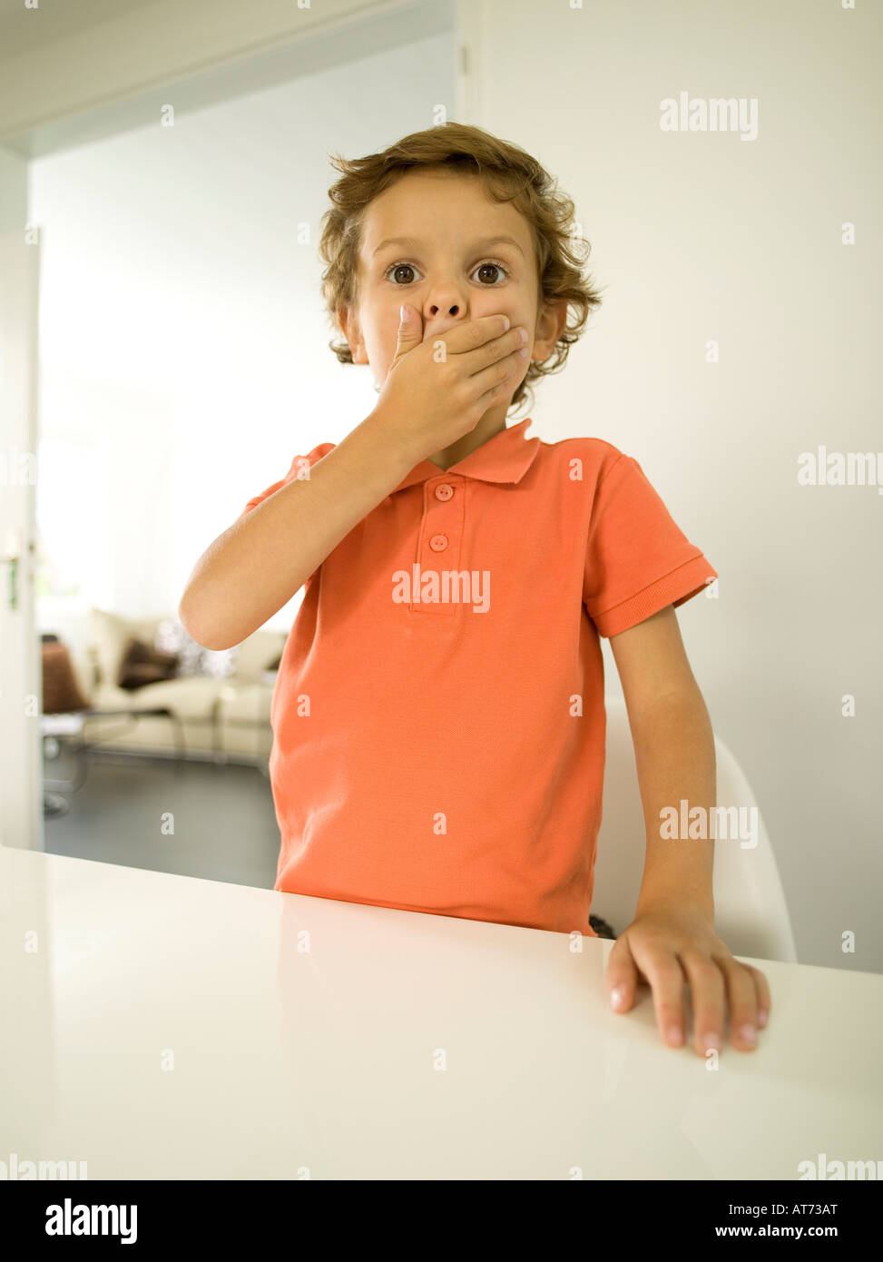Young boy (4-5) covering his mouth with his hands, portrait - Stock Image