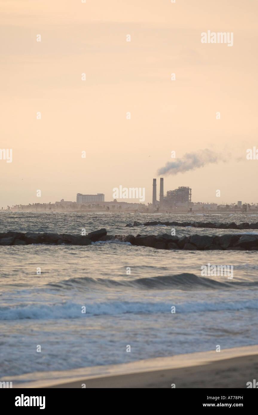 Smokestacks in the distance along the shoreline between Newport Beach and Huntington Beach highlight energy needs. - Stock Image