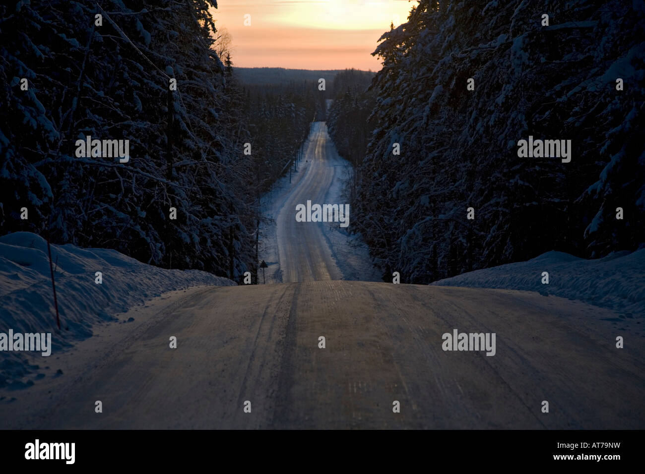 Scene of an empty, icy country road through forest at Winter at evening Finland Stock Photo