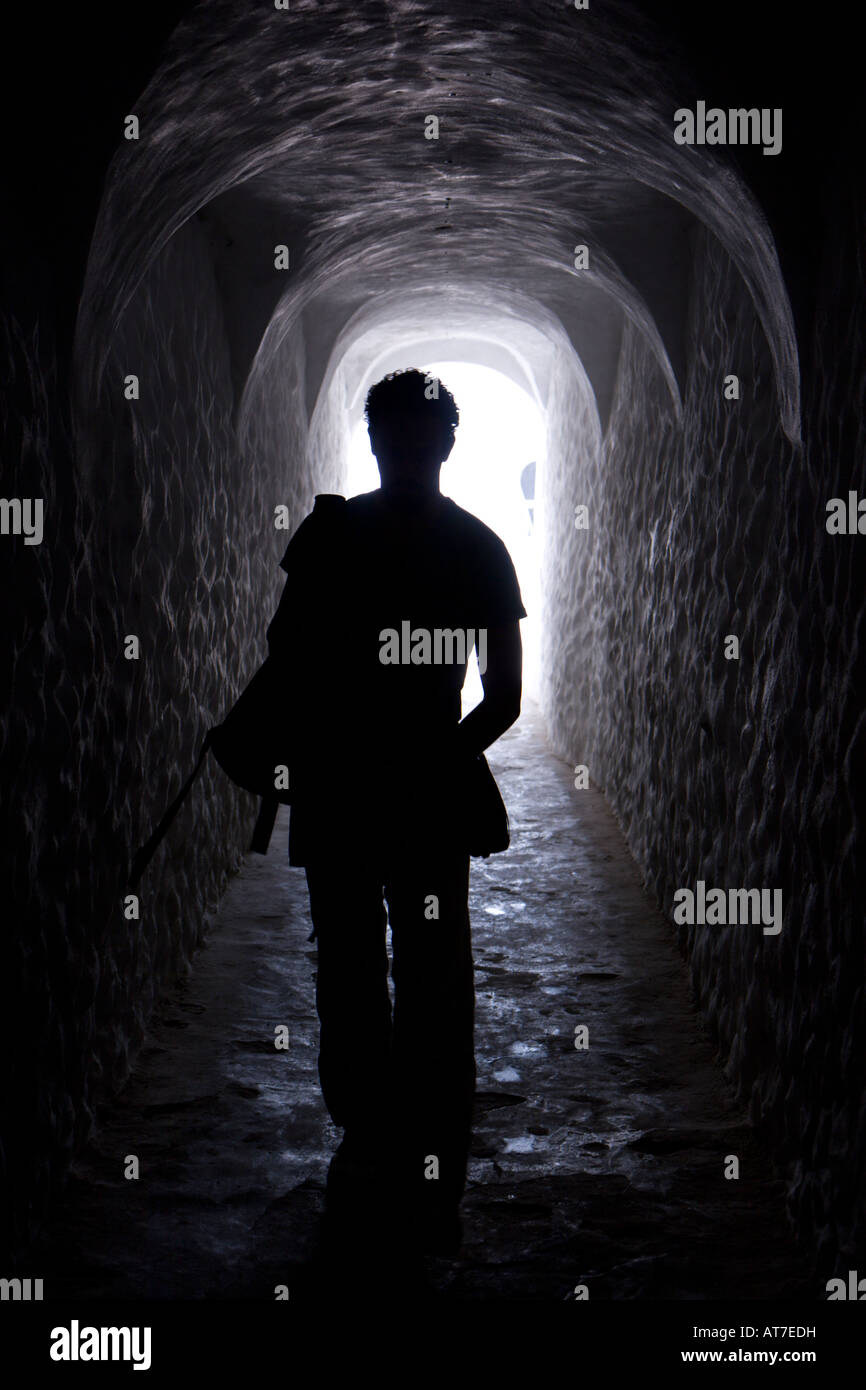 A man walks down a hall in Elmina Castle on a tour of the former slave fort Stock Photo