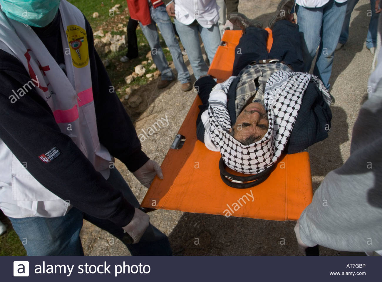 A Palestinian is evacuated after Israeli troops responded to stone-throwing with tear gas at the West Bank village - Stock Image