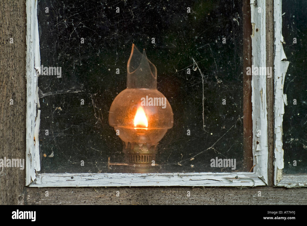 old oil lamp with broken glass burning at window of a timber wooden house - Stock Image
