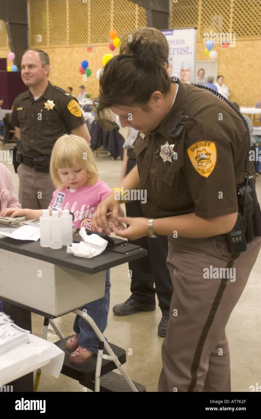 Deputy Retchless fingerprinting young child during a healt fair for a Children's ID kit. Nebraska, USA. - Stock Image