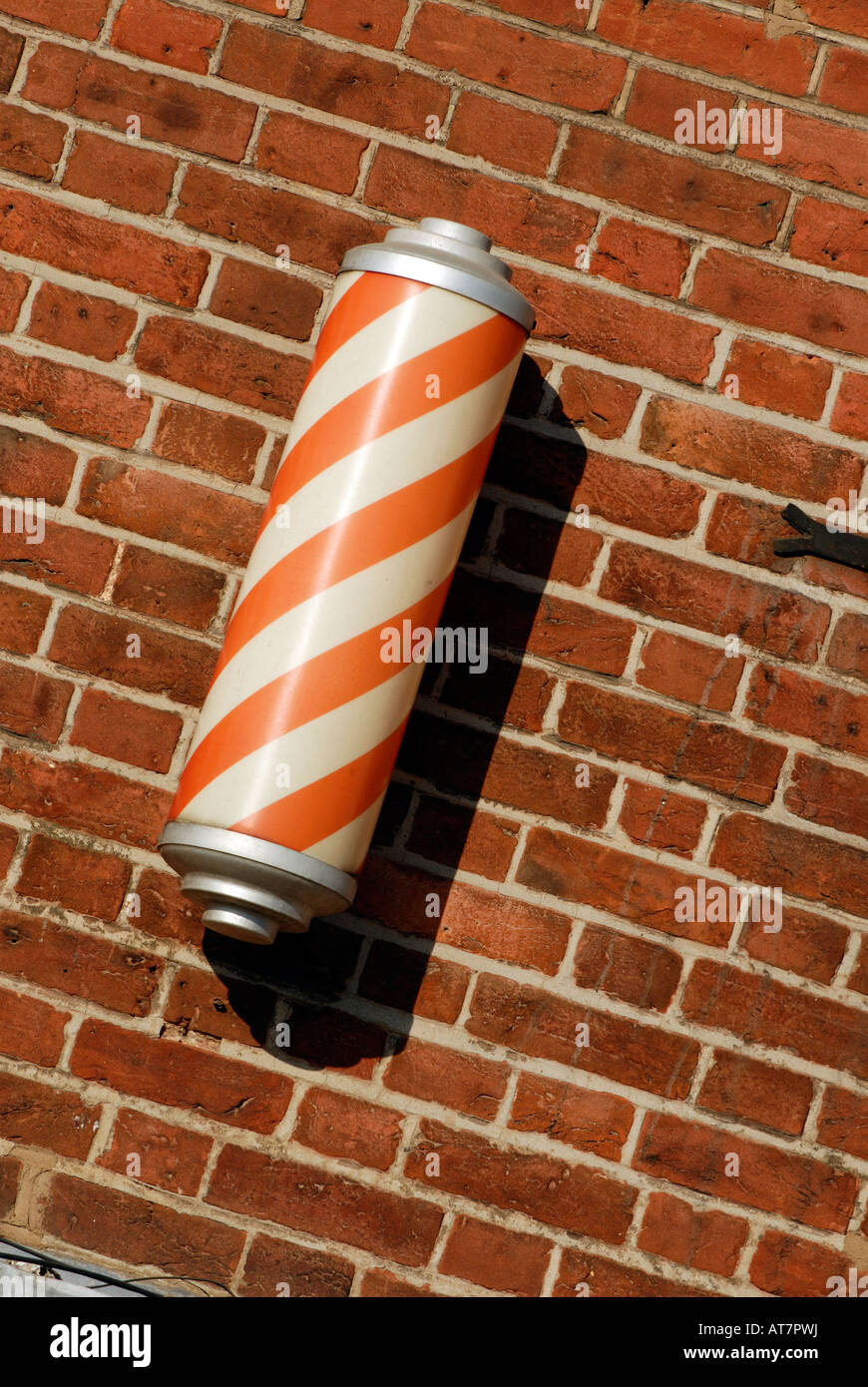 a barbers pole in red and white spirals striped outside of a traditional barbers shop in a village - Stock Image