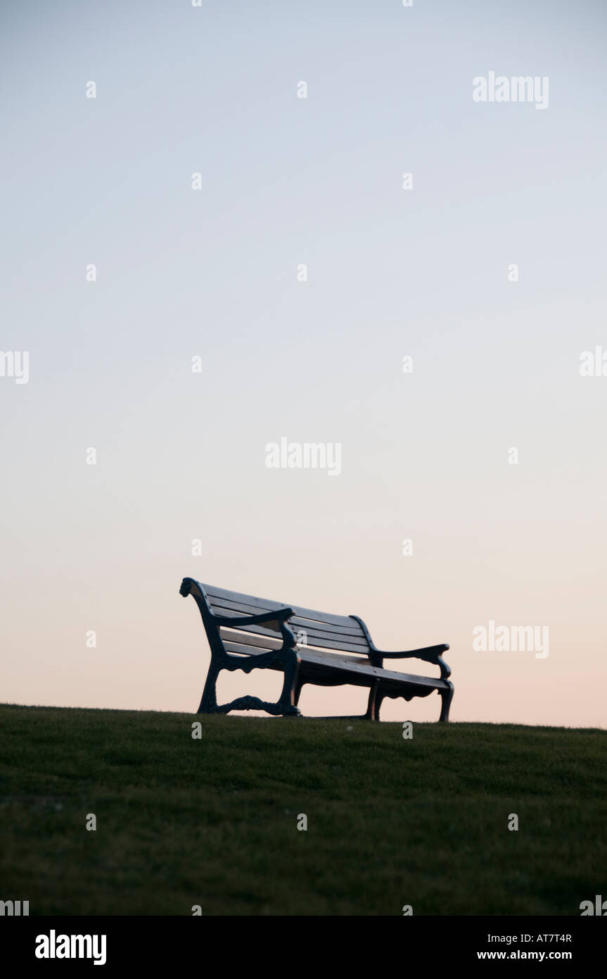 empty park bench at dusk twilight silhoueted against the twilight evening sky at sundown - Stock Image