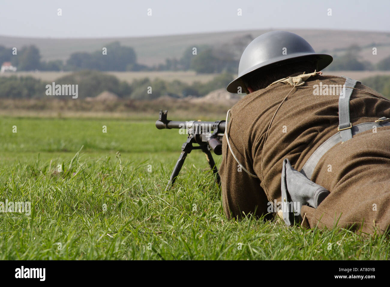 WW2 soldier armed with a machine gun lying low - Stock Image