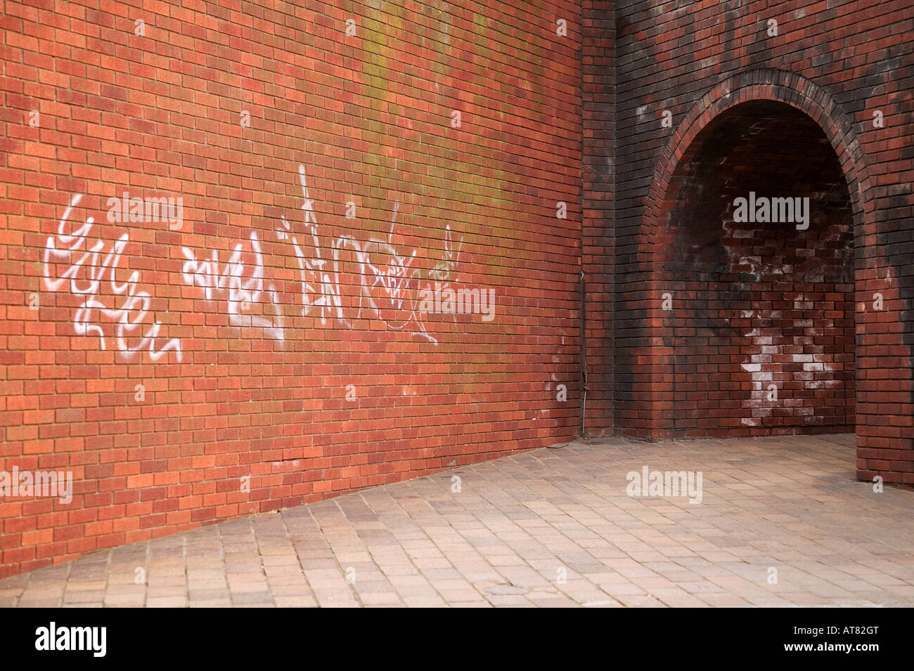 Inner city shot of a brick wall and archway leading into the unknown - Stock Image