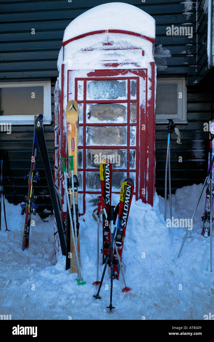 Red Telephone box surrounded by snow and skis, Cairngorms National Park Glenshee ski centre Aberdeenshire and Perthshire - Stock Image