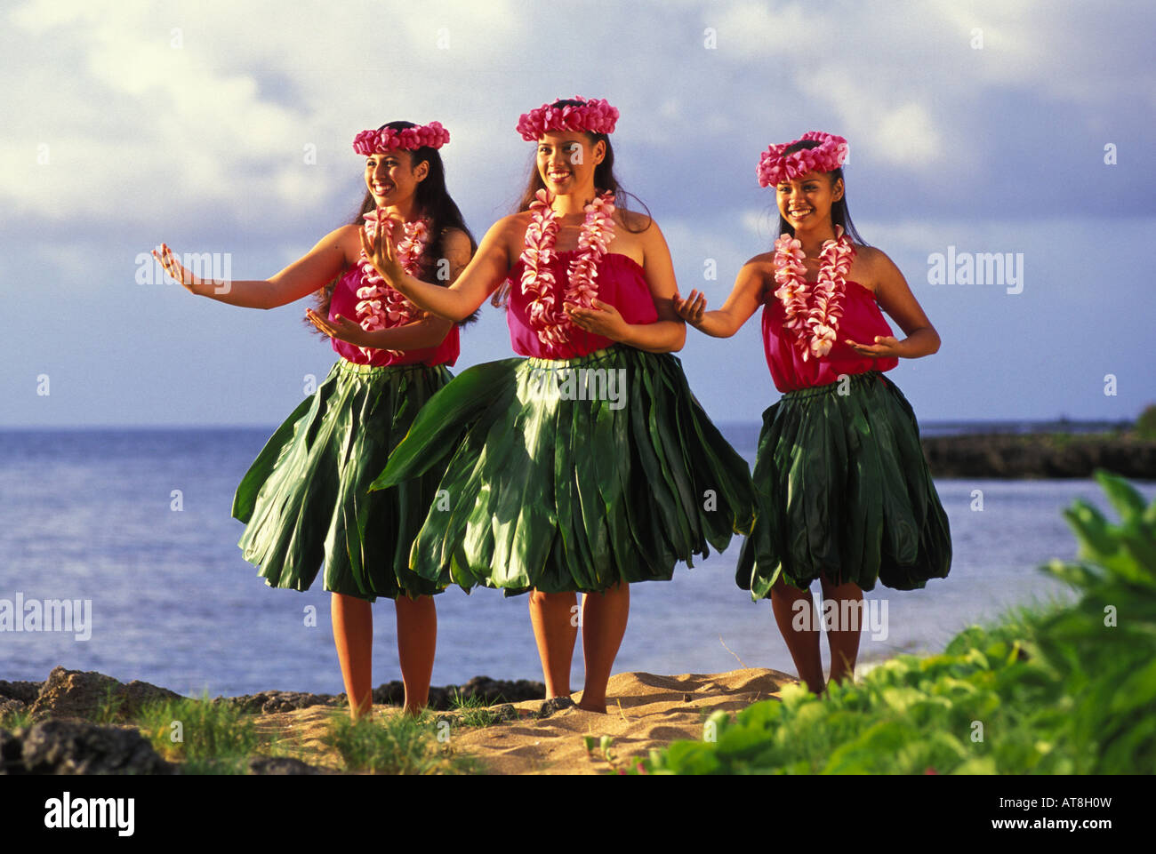Three hula dancers with plumeria leis and ti leaf skirts near ocean - Stock Image
