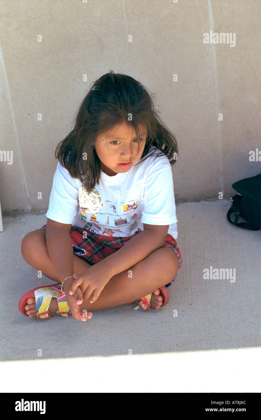 Pensive girl age 6 with legs crossed sitting on sidewalk. Sault Ste. Marie Michigan USA - Stock Image