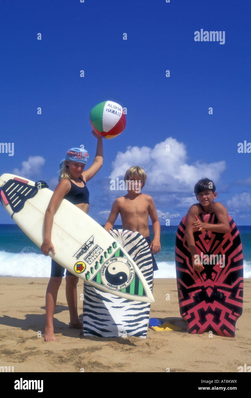 Kids with surfboards near ocean at Secret Beach, Kauai Stock Photo