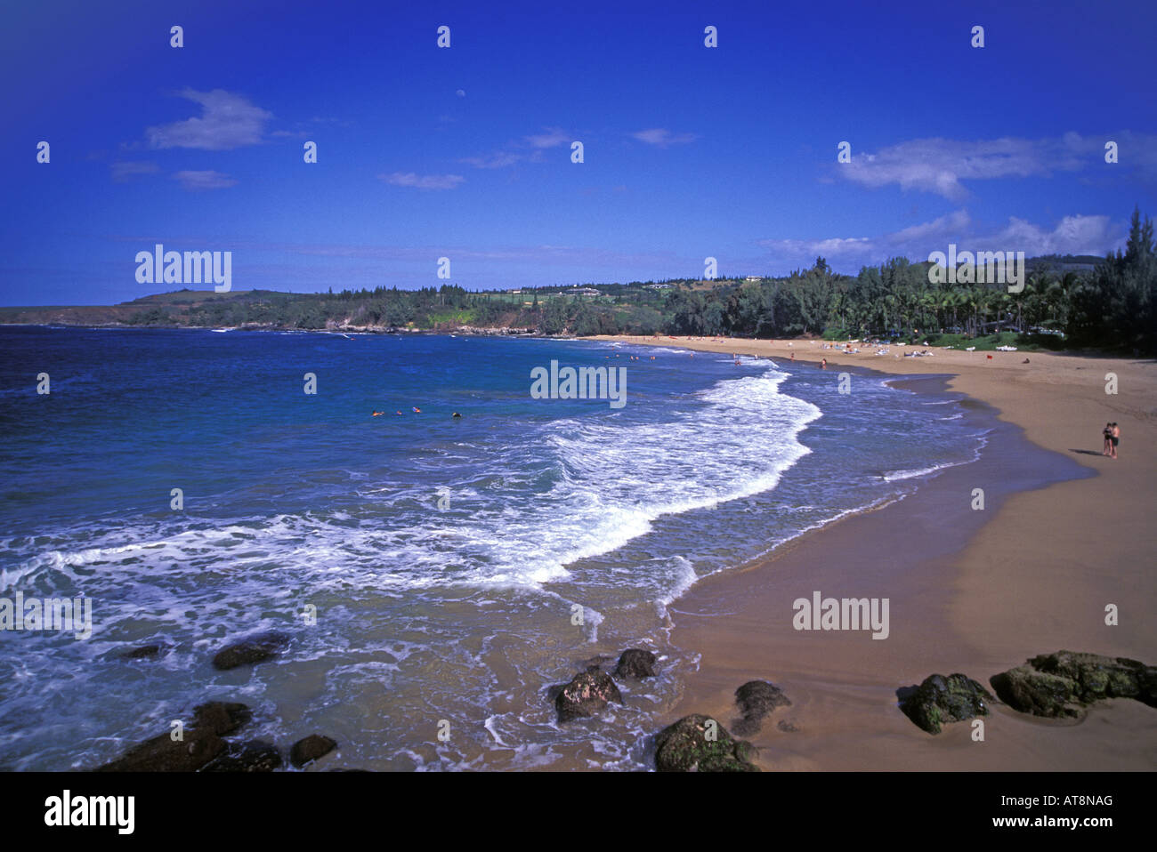 A sprinkling of tourists dot the secluded Flemings Beach Park at Kapalua on the island of Maui. - Stock Image