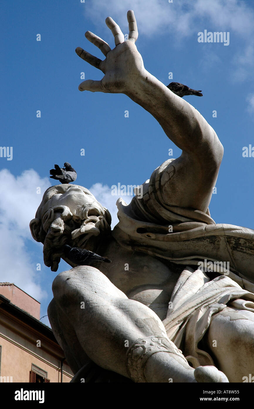 A figure in Bernini's 'Four Rivers' fountain in Rome shades his eyes. Due to rival Borromini's facing church? Or maybe pigeons? - Stock Image