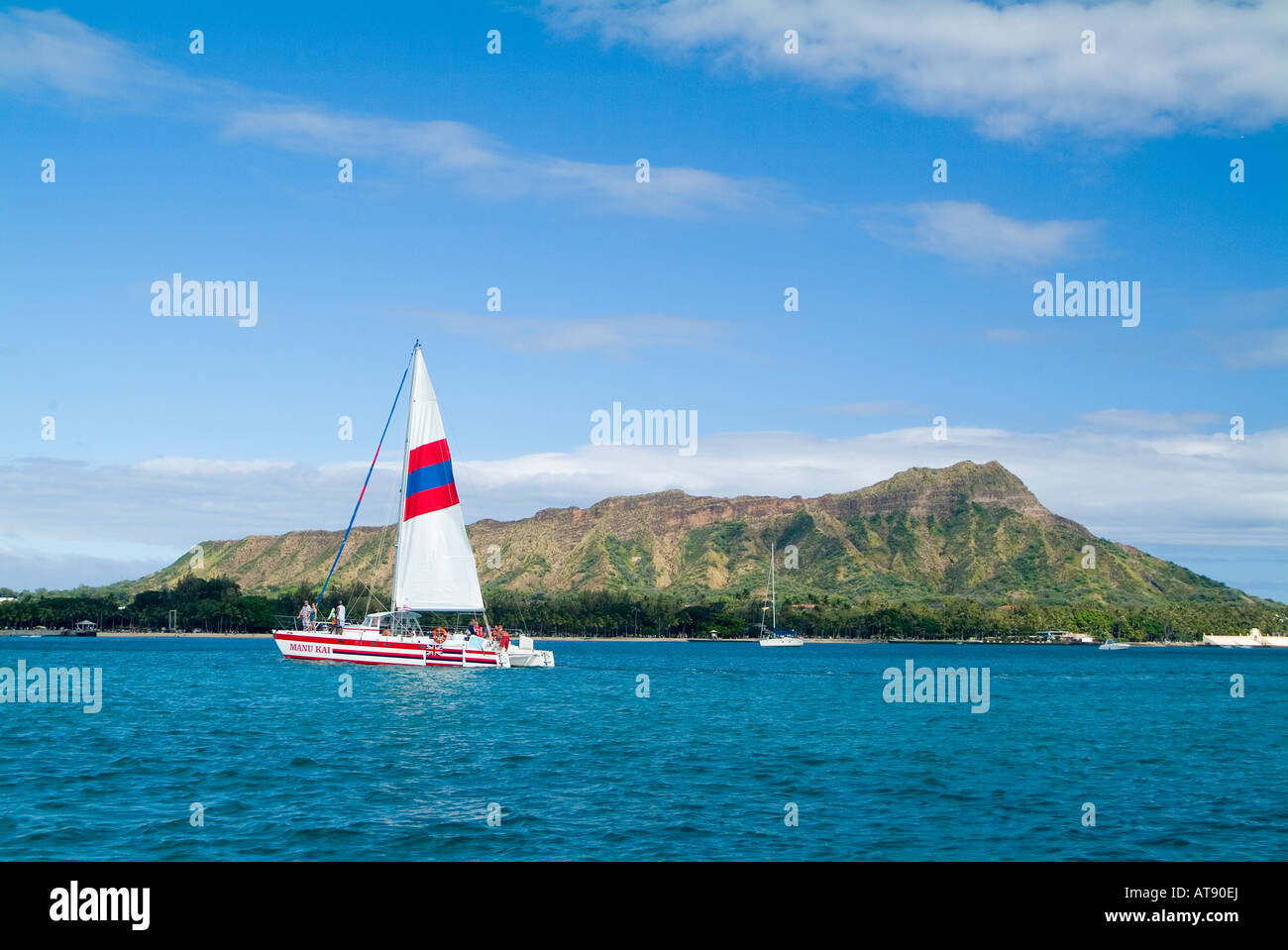 A catamaran cuts a path on the clear blue water in front of Diamond Head, Stock Photo