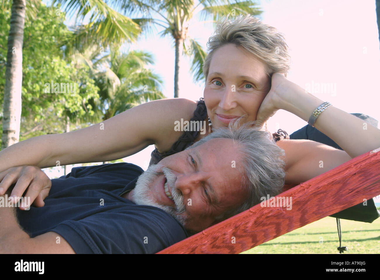 A couple relaxes in a hammock at Queens Beach, Waikiki. Stock Photo