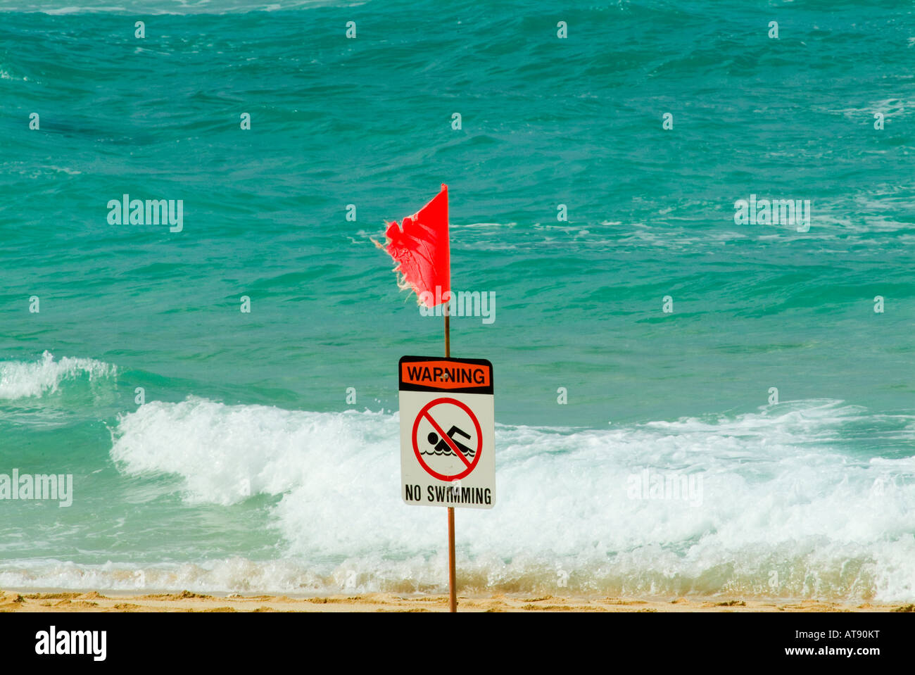 A red flag warns swimmers of high surf at the north shore on the island of Oahu. Stock Photo