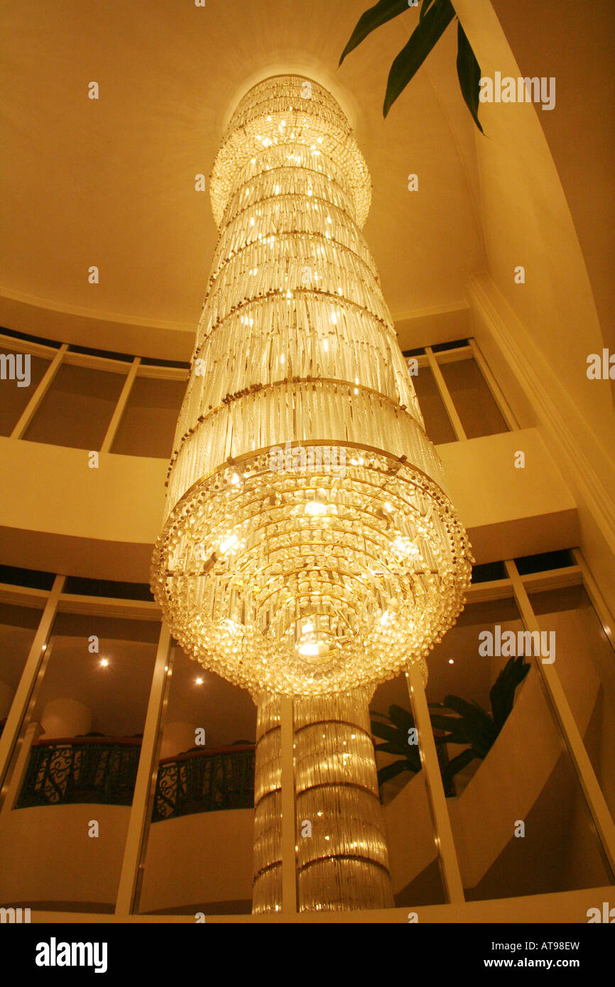 Huge ornate crystal glass chandelier casts soft golden glow in hotel huge ornate crystal glass chandelier casts soft golden glow in hotel lobby lounge creating a classy and luxurious ambience aloadofball Images