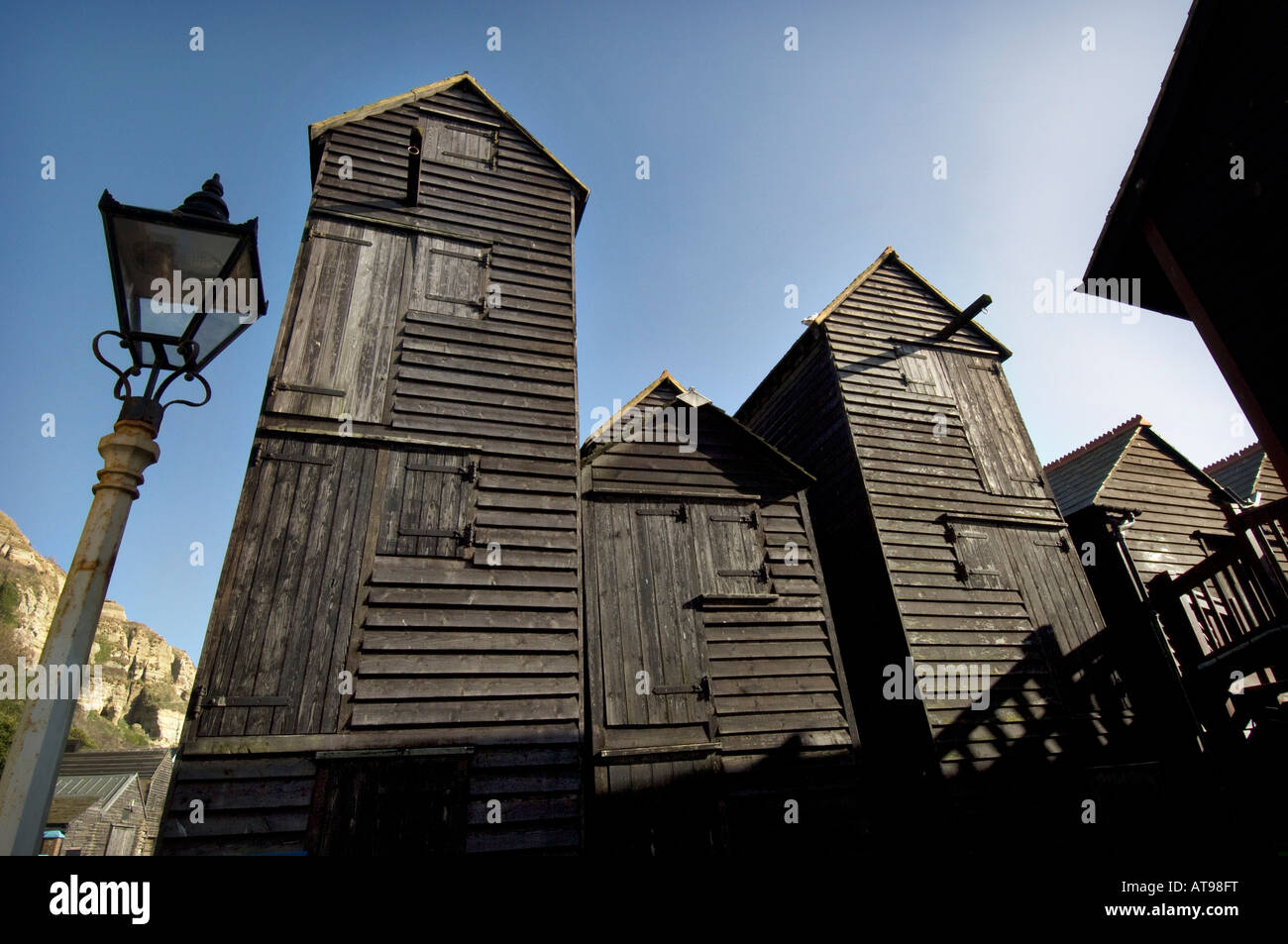 Victorian Net Shop huts in the Old Town by Hastings beach The tall black wooden net shops were built to store fishing - Stock Image
