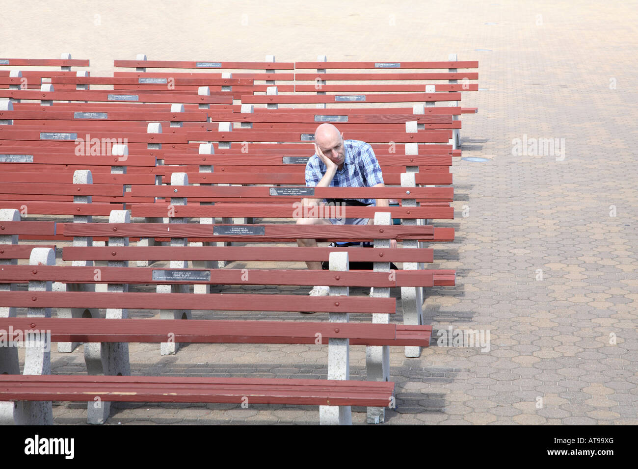 Rows of concrete and wooden seats on brick tiled paving.  All empty except one solitary man sitting on end of row - Stock Image